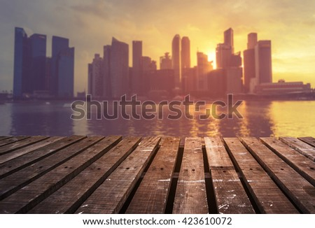 Wooden terrace with the city blur background during sunset - stock photo