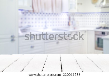 Wooden textured table over blurred kitchen interior background