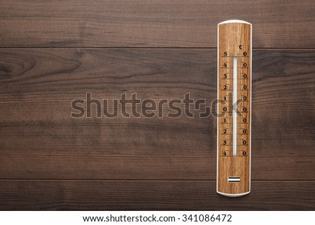 wooden thermometer on the brown table background - stock photo