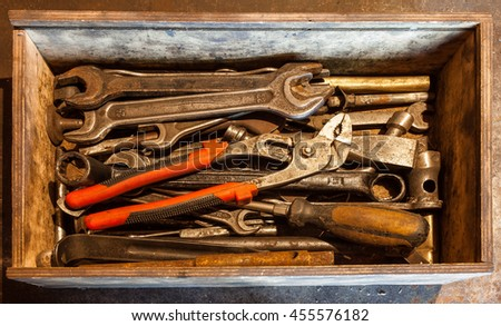 Wooden tool box of hand tools with old and dirty, rusty wrenches, ring spanners, pliers, screwdrivers, chisel and other do-it-yourself (DIY) tools. - stock photo