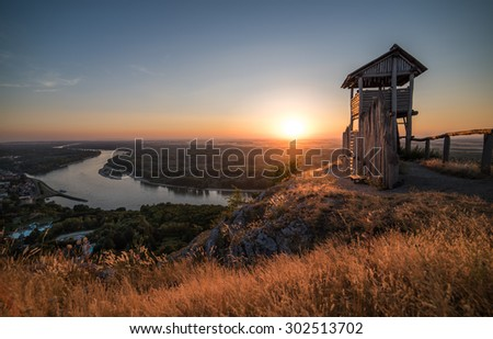 Wooden Tourist Observation Tower above a Little City of Hainburg an der Douna with Danube River at Beautiful Sunset - stock photo