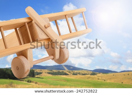 wooden toy airplane against blue sky and green field - stock photo