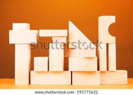 Wooden toy blocks on table on yellow background - stock photo