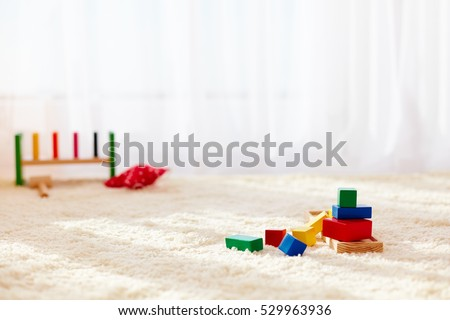wooden toy bricks strewn on the carpet in playroom, at sunny day