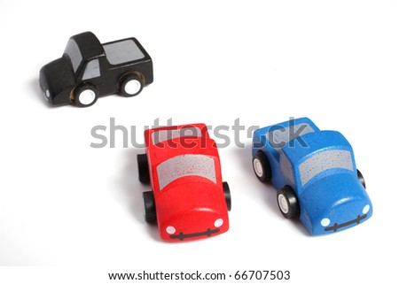 Wooden toy cars in red, blue and black isolated on white background - stock photo