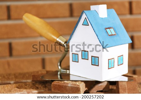 Wooden toy house on trowel and tiles on brick wall background