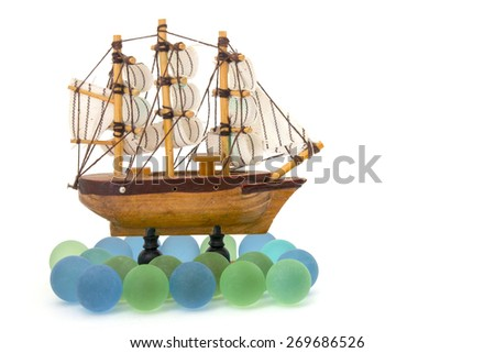 wooden toy ship at sea isolated over white - stock photo