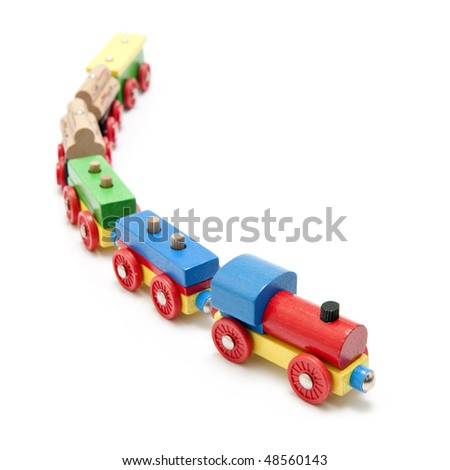 Wooden toy train with a locomotive and five carriages with a subtle reflection on a white background and a shallow depth of field - stock photo