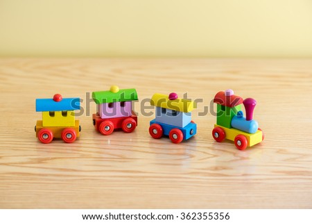 Wooden toy train with colorful blocs isolated on a wooden background