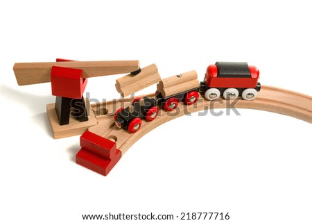 Wooden toy with magnet crane plunges into the wagon unit, which stands on railroad isolated on white background - stock photo