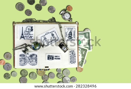 Wooden travel box with stickers of fabric, banknotes and coins, watches, metal pendants in the form of the globe and the camera on an isolated background. Top view - stock photo