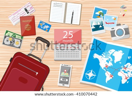 Wooden travellers table, paper map of world and tourist equipment, travel bag, passport, airplane ticket, notebook, smartphone with navigation application, photo camera, cash and coins, calendar  - stock photo