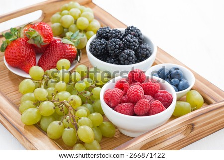 wooden tray with fresh berries and grapes, horizontal