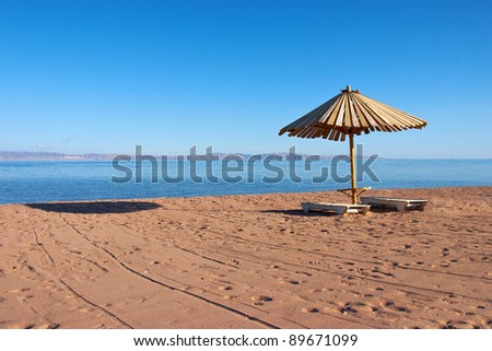 Wooden umbrella and chairs on the beach - stock photo