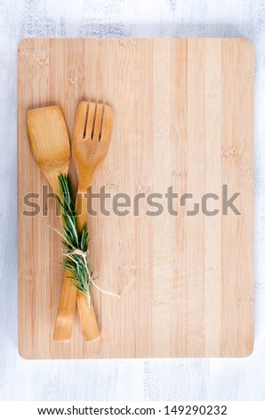 wooden utensils tied with rosemary on bamboo chopping board from overhead, food background - stock photo