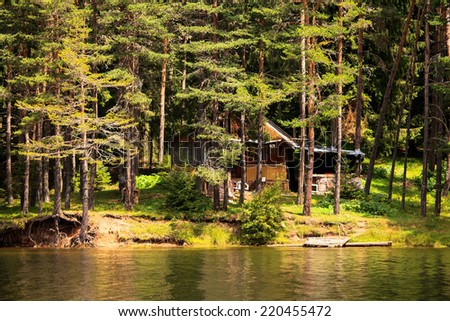 wooden villa in autumn forest on lake beach in bulgarian mountains  - stock photo