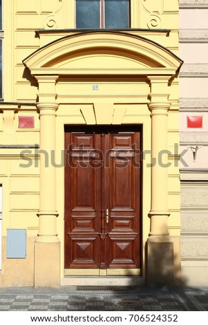Wooden vintage entry door decorated with arch and tuscan order columns. Prague. Czech Republic.
