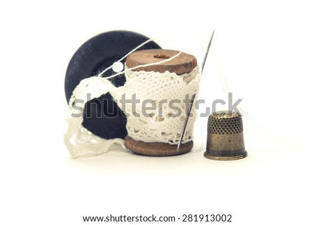 wooden vintage spool for thread wound with white lace for sewing, needle, black wooden button and a metal thimble on white background - stock photo