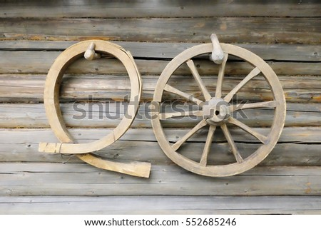 wooden wagon wheel on the wall of the old house