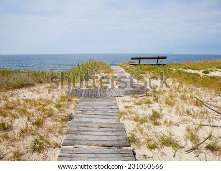 wooden walking path and bench on  beach of  Baltic Sea. Curonian Spit, Lithuania  - stock photo