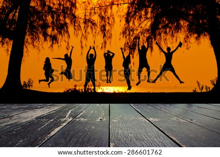 Wooden walkway and silhouette of friends jumping on beach - stock photo