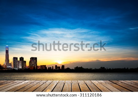 Wooden walkway at riverside on city and soft blue sky in sunset time background
