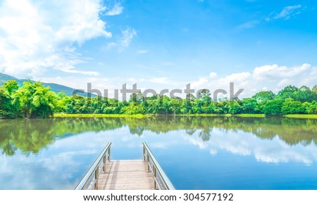 Wooden walkway in lake with moutain and clear sky background . - stock photo