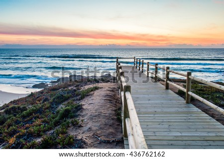 Wooden walkway on the Atlantic ocean coast in the sunset time in Alentejo, Portugal