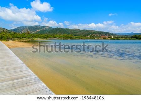 Wooden walkway to Chia beach along a salt lake on sunny summer day, Sardinia island, Italy - stock photo