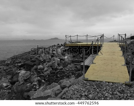 wooden walkway with lookout point and sea background selective color