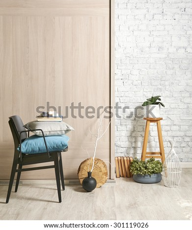 wooden wall interior with black chair and green flower  - stock photo