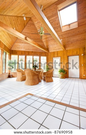 Wooden Wall Sun Room Interior with Natural Wicker Furniture, Ceramic  Tile floor - stock photo
