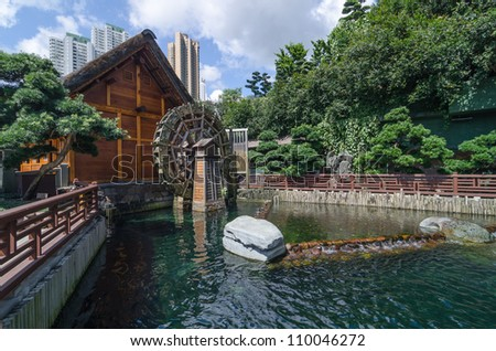 Wooden water wheel mill and pool in garden - stock photo