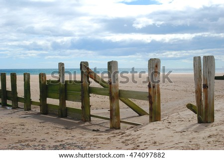 wooden weathered sea barrier and beach at Spittal