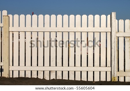 Wooden white fence on the beach - stock photo