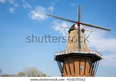 Wooden Windmill in Holland, Michigan - An authentic wooden windmill from the Netherlands rises behind a field of tulips in Holland Michigan at Springtime. - stock photo