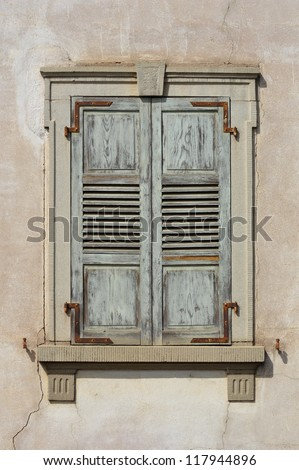 Wooden window shutters - Closed old shuttered weathered wooden window in the Alsace, France - stock photo