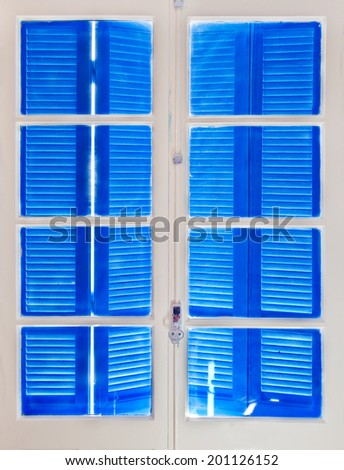 Wooden window with blue shutters closes, view from inside - stock photo