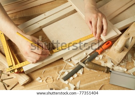 Wooden workshop table with tools. Man's arms measuring. - stock photo