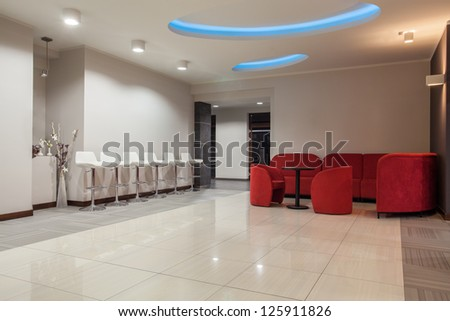 Woodland hotel - Waiting room with stools and sofa - stock photo