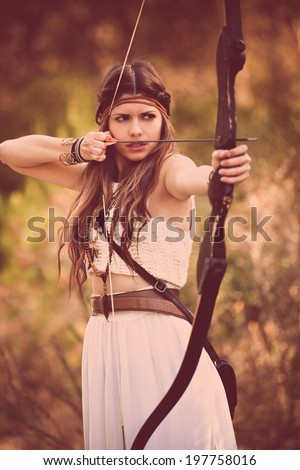 woodland hunter woman with bow and arrow - stock photo
