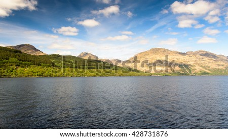 Woodland lines mountainsides on the shores of Loch Lomond in the West Highlands of Scotland. - stock photo