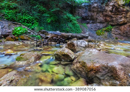Woodland waterfall flowing over rocks - stock photo
