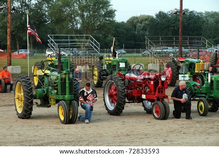 WOODSTOCK, IL - AUGUST 05: Tractors Farmall F-14 model 1938 and John Deere model A 1937 at the Farmers fair and machinery exhibition on August 5, 2010 in Woodstock, IL - stock photo