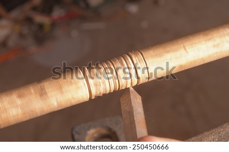 Woodworker turning a chair leg on a lathe - stock photo