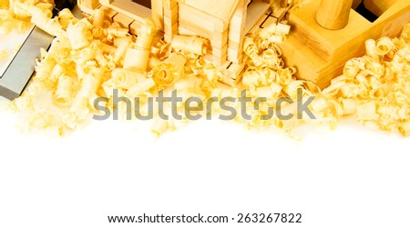 Woodworking. House construction. Joiner's works. The small wooden house, chisel, plane and shaving on white background. - stock photo