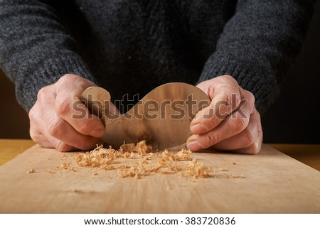 Woodworking tool. Carpenter saving wood with card scraper blade. - stock photo