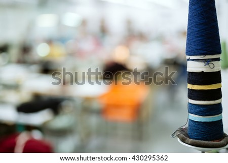 Wool and thread spools on desk used in textile industry - stock photo