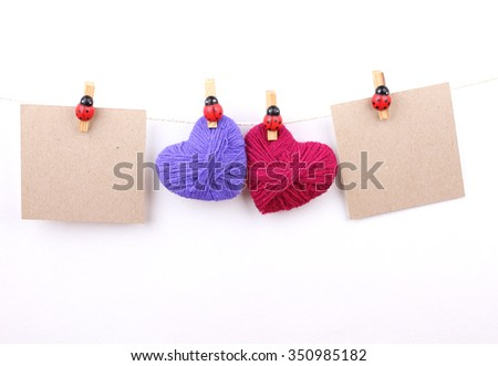 Wool Love Valentine's hearts and paper card, wood bug clips hanging on white background, copy space - stock photo