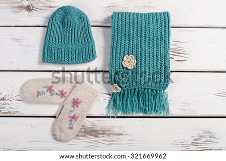 Wool scarf, hat and mittens on a wooden background. Winter handmade set of things. - stock photo